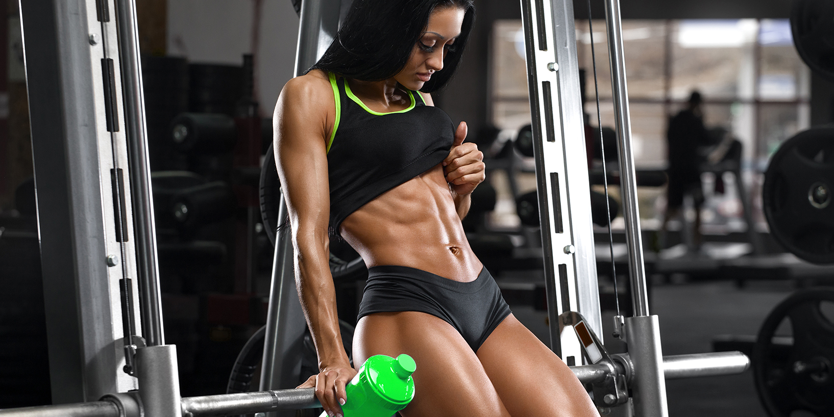 woman with really defined abs holding green shaker bottle