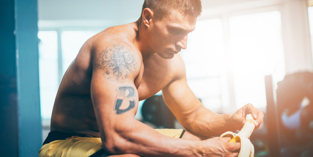 bodybuilder eating a banana