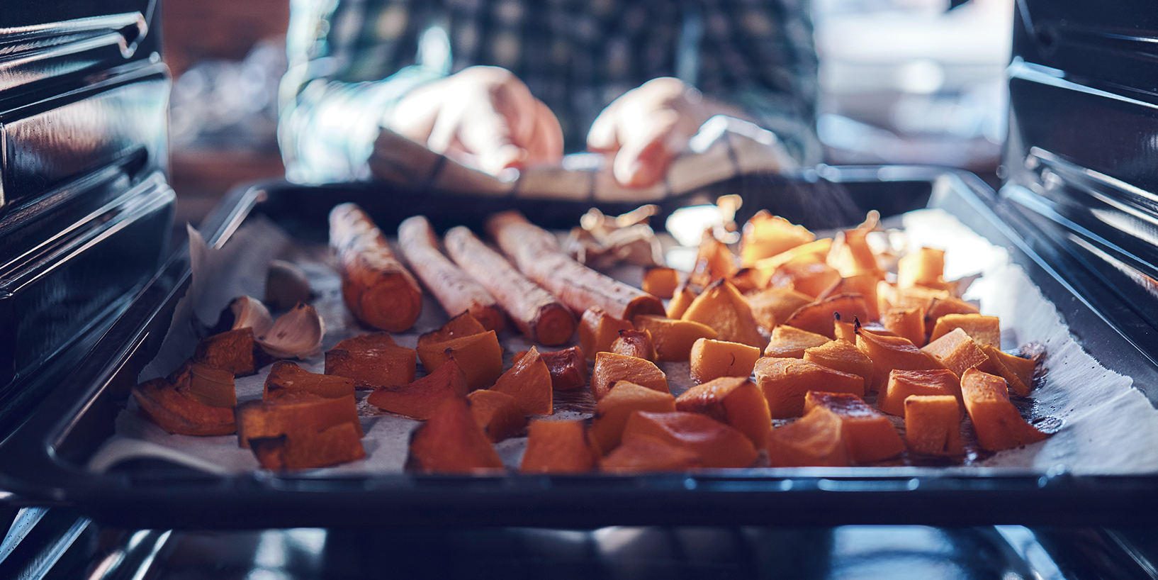 Someone pulling sweet potatoes out of the oven. Holiday meal
